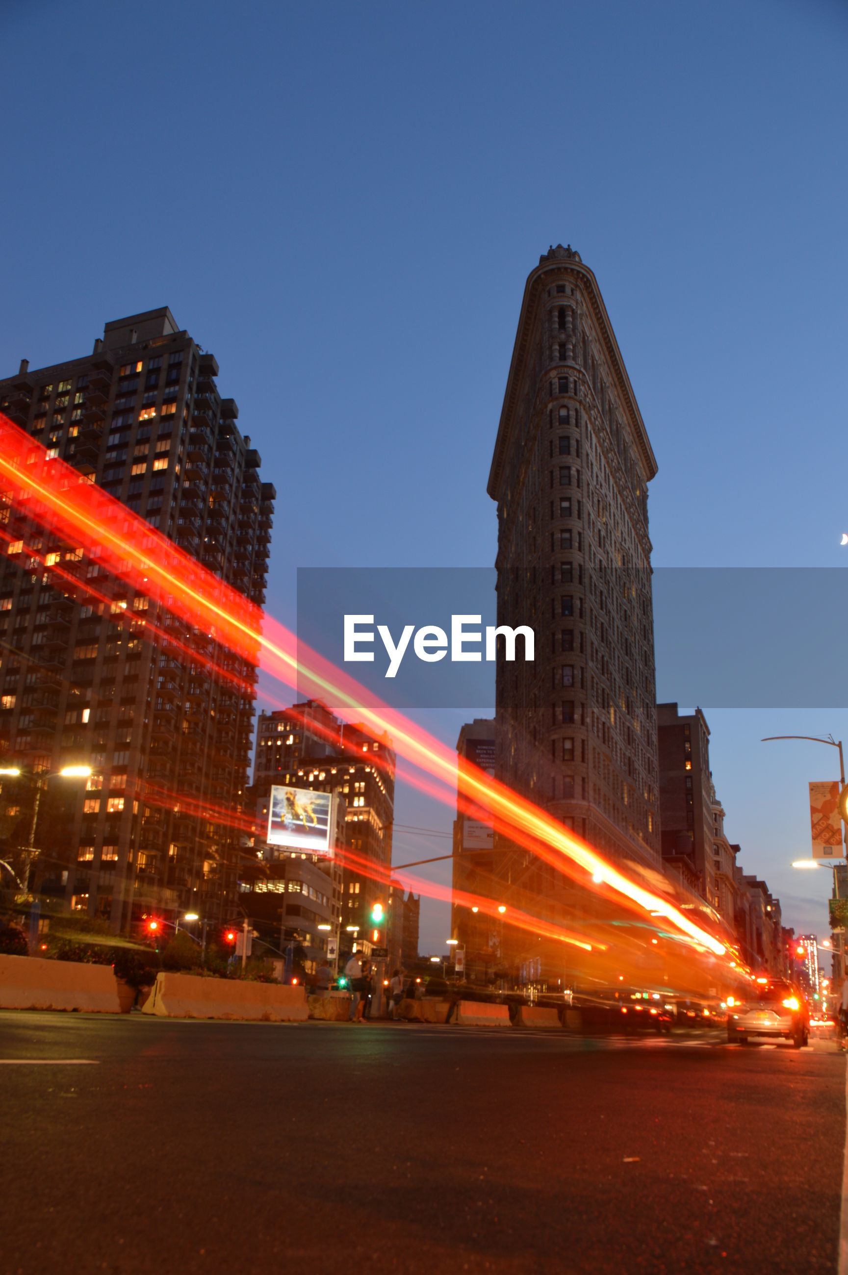 Light trails on city street by flatiron building at night in new york city.