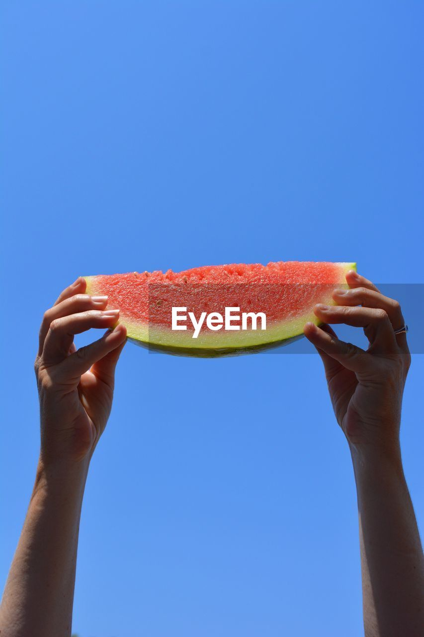 Close-Up Of Hands Holding Watermelon Against Blue Sky
