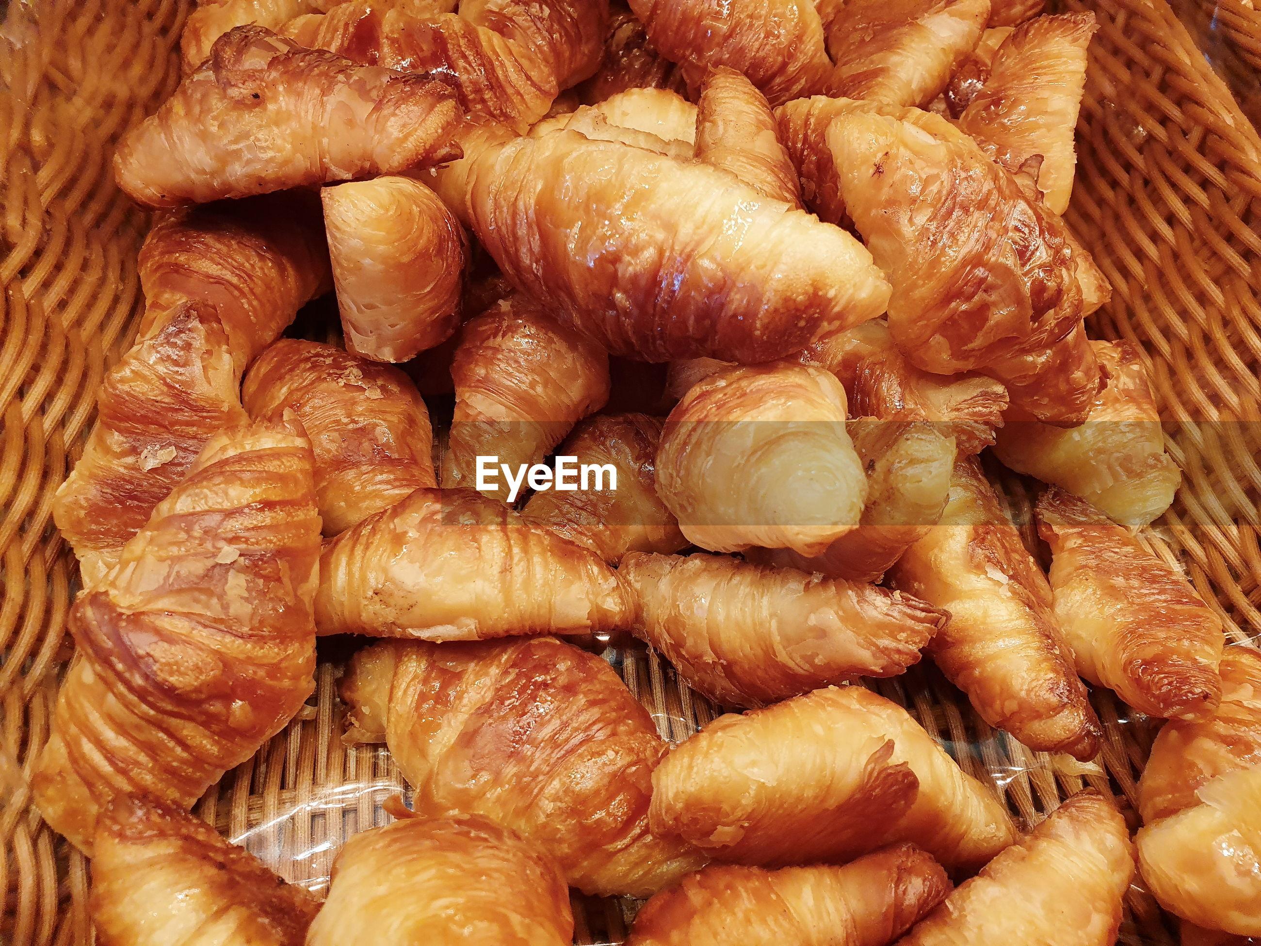 Freshly baked croissants in a wicker basket.