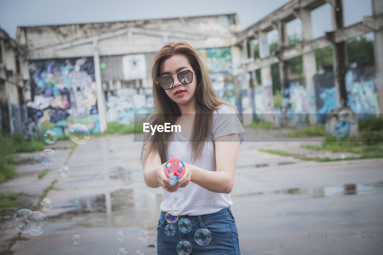 one person, real people, front view, young adult, portrait, glasses, three quarter length, long hair, looking at camera, casual clothing, standing, young women, sunglasses, focus on foreground, architecture, leisure activity, lifestyles, hairstyle, fashion, hair, outdoors, beautiful woman, teenager