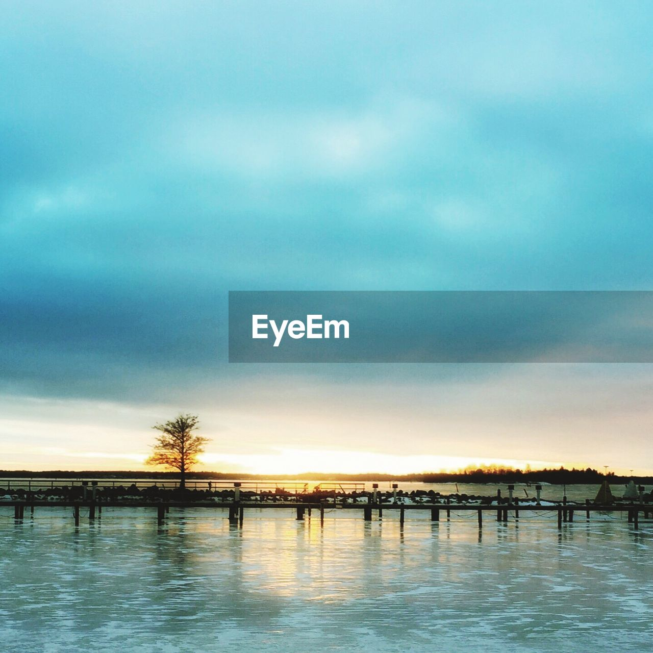 sky, cloud - sky, water, tranquility, sunset, nature, beauty in nature, tranquil scene, scenics, outdoors, waterfront, no people, built structure, bridge - man made structure, architecture, tree, lake, day