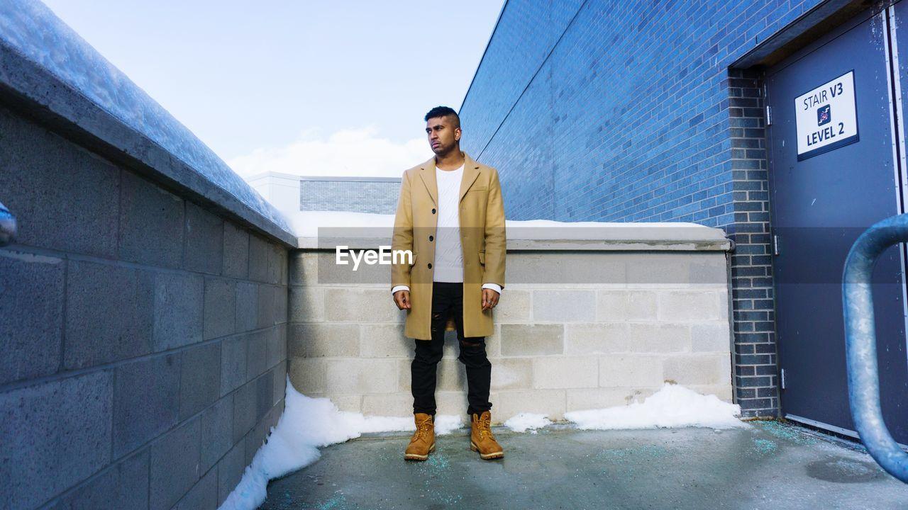 Full Length Portrait Of Man Standing In City In Winter