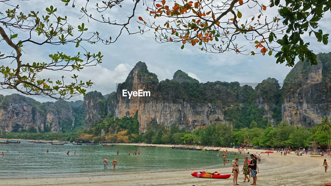 Tourist visiting railay beach against sky