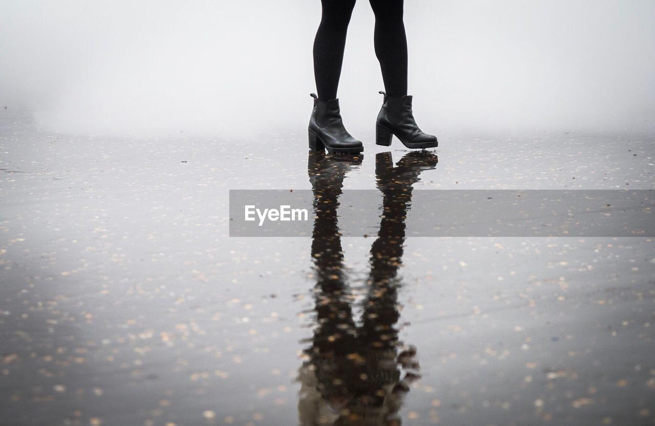 Low Section Of Woman Walking On Wet Street