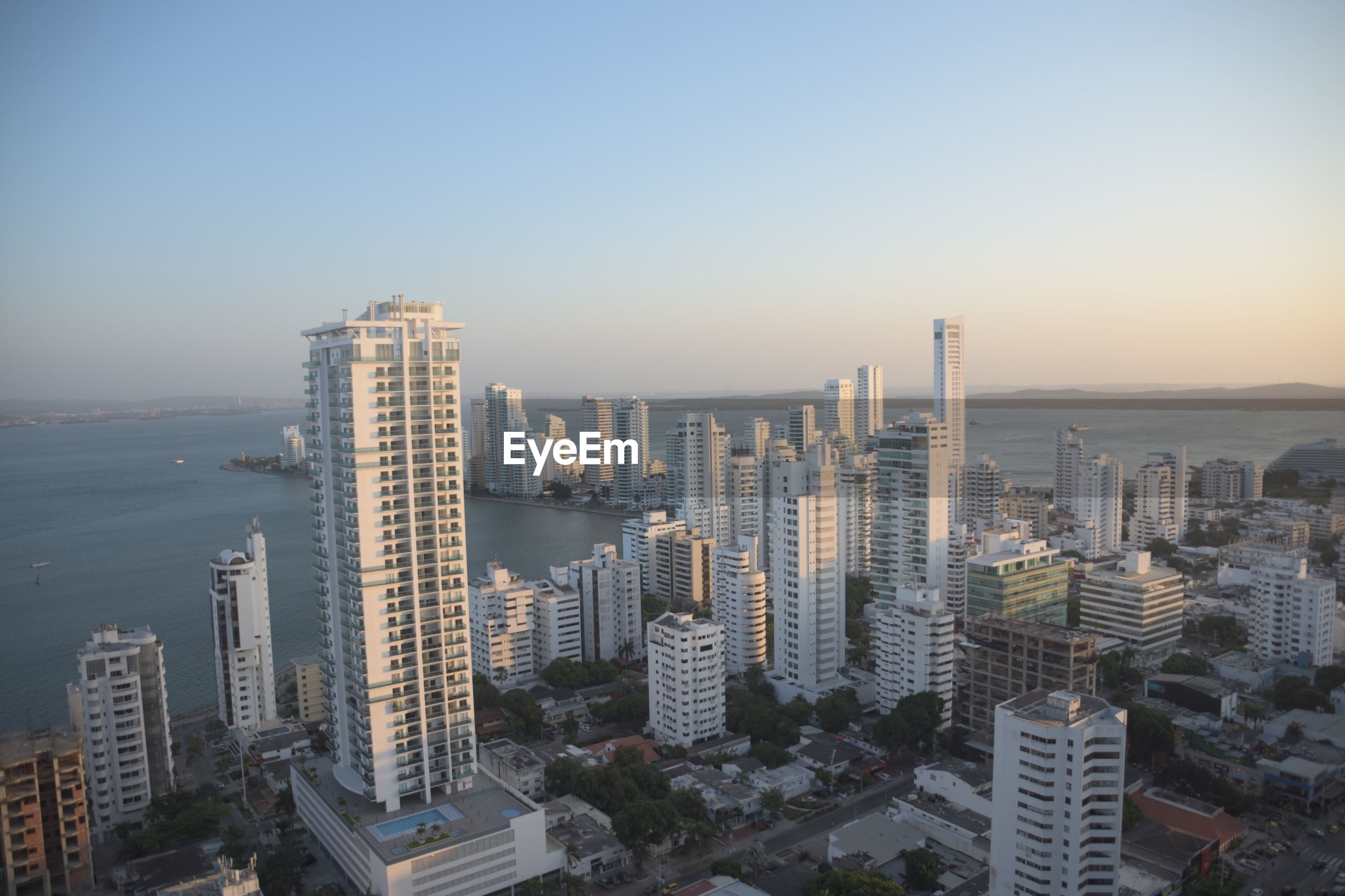 AERIAL VIEW OF BUILDINGS AGAINST SKY IN CITY AGAINST CLEAR BLUE BACKGROUND