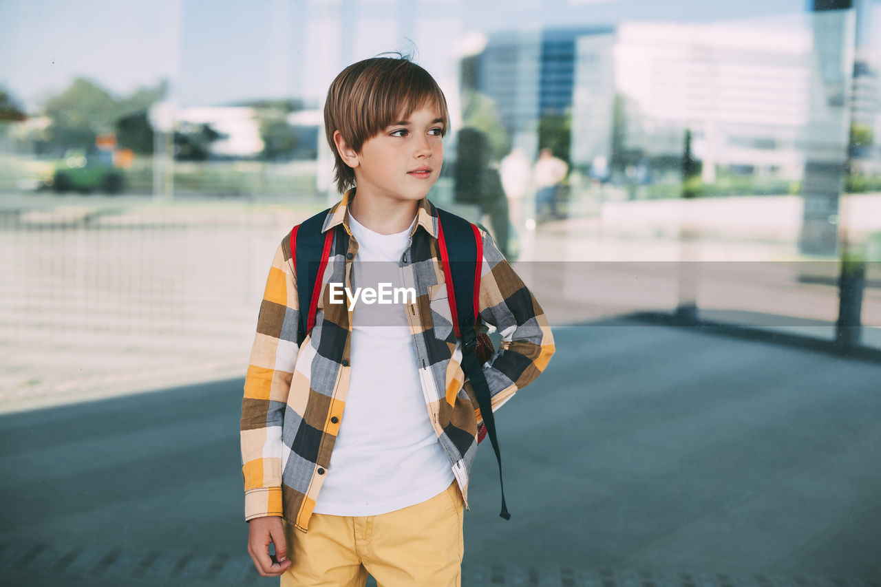 Full length of boy standing on road in city