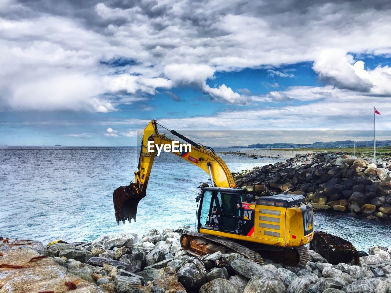 Earth Mover On Rocks By Sea Against Cloudy Sky