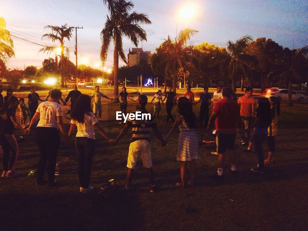 tree, sunset, large group of people, real people, leisure activity, sky, night, men, full length, outdoors, standing, lifestyles, togetherness, illuminated, women, palm tree, friendship, water, crowd, nature, people, adult