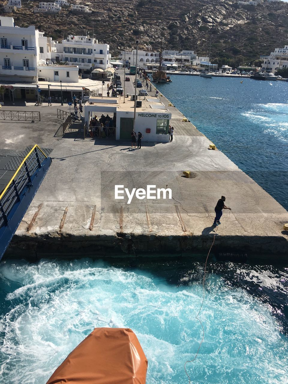 High angle view of boat by man holding rope at jetty