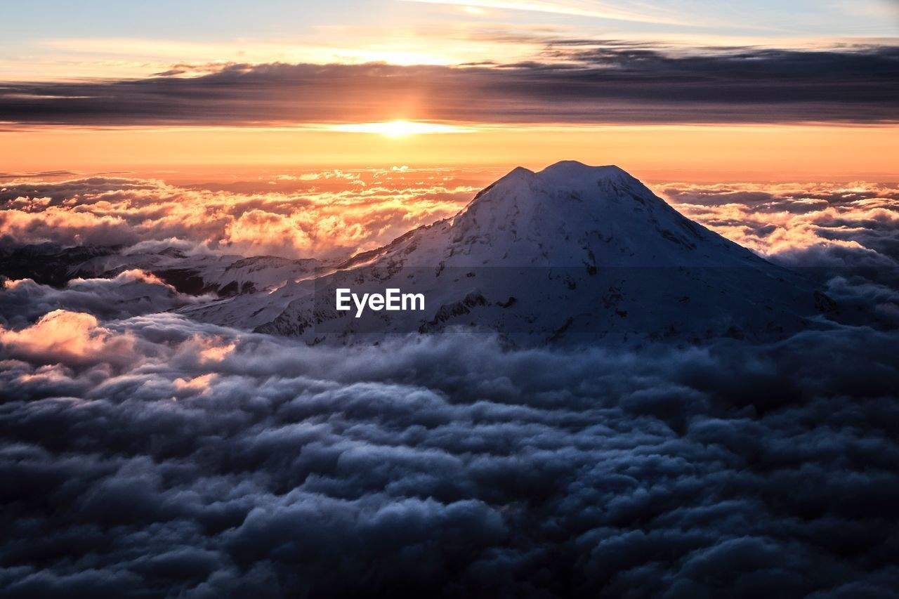 Idyllic shot of mt rainier amidst clouds against sky during sunset