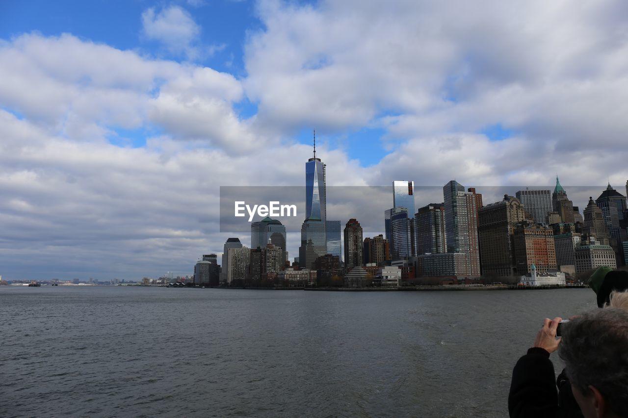 SEA BY MODERN BUILDINGS AGAINST SKY