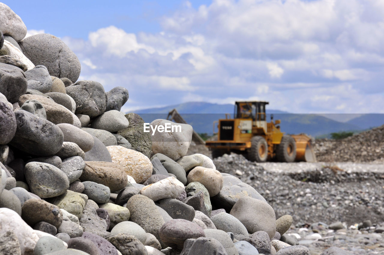 solid, rock, sky, rock - object, cloud - sky, nature, transportation, day, construction industry, land, no people, stone - object, construction machinery, construction site, earth mover, land vehicle, pebble, mode of transportation, outdoors, industry, gravel