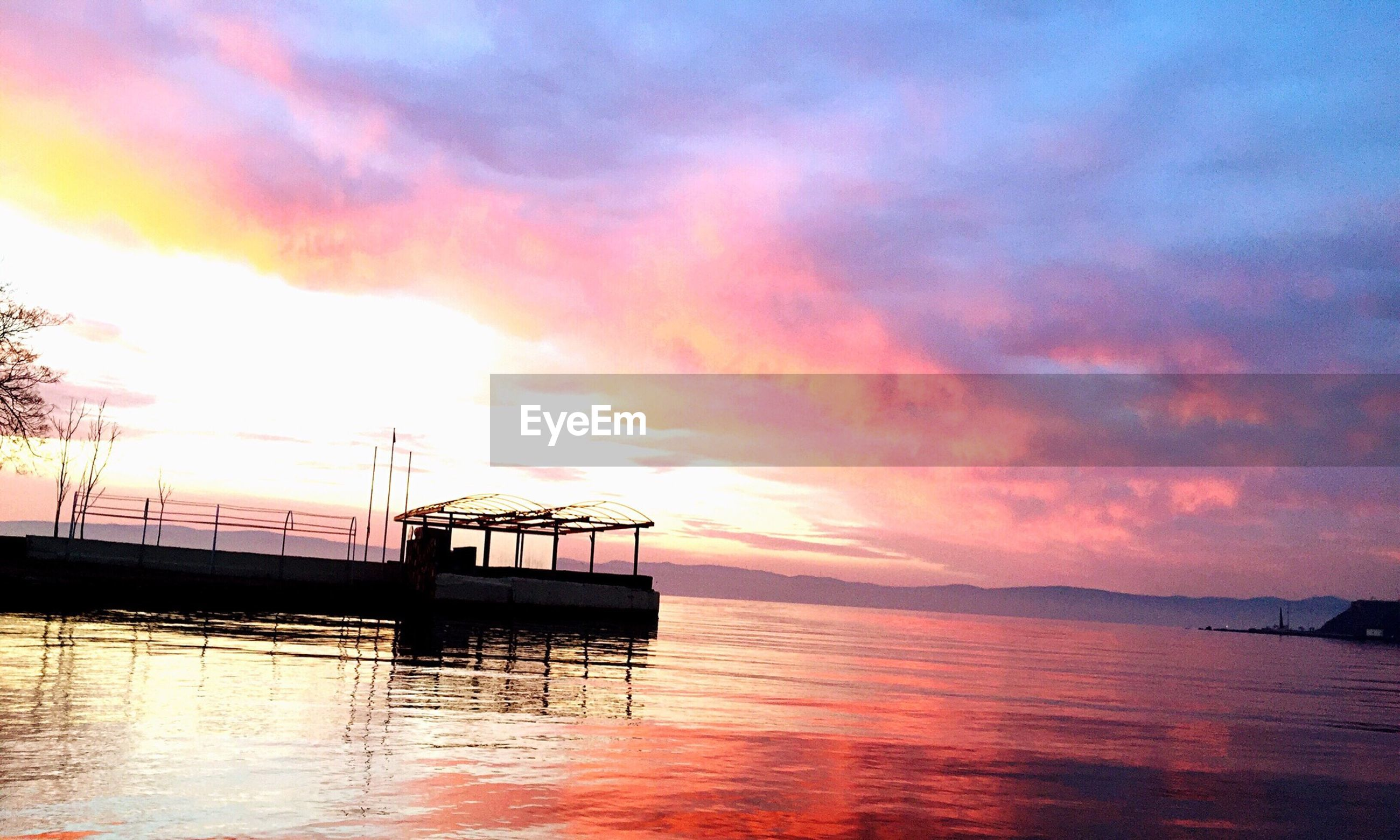 sunset, water, sky, tranquility, scenics, tranquil scene, cloud - sky, beauty in nature, sea, orange color, waterfront, idyllic, nature, reflection, cloudy, cloud, horizon over water, pier, dramatic sky, lake
