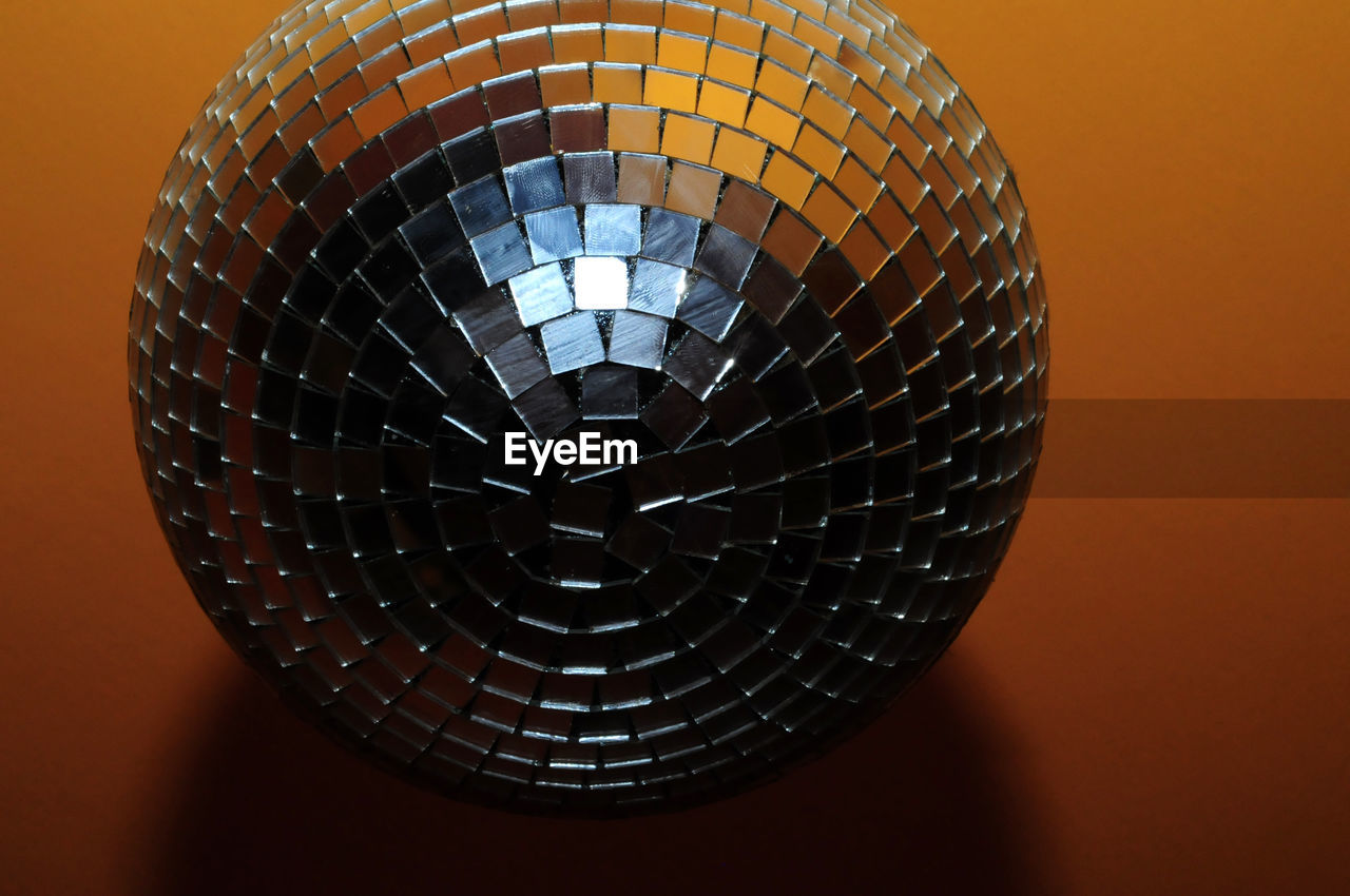indoors, pattern, no people, close-up, technology, orange color, shape, design, illuminated, geometric shape, lighting equipment, still life, circle, decoration, ceiling, light, low angle view, arts culture and entertainment, single object, sphere, electric lamp, nightlife, directly below, light fixture, silver colored