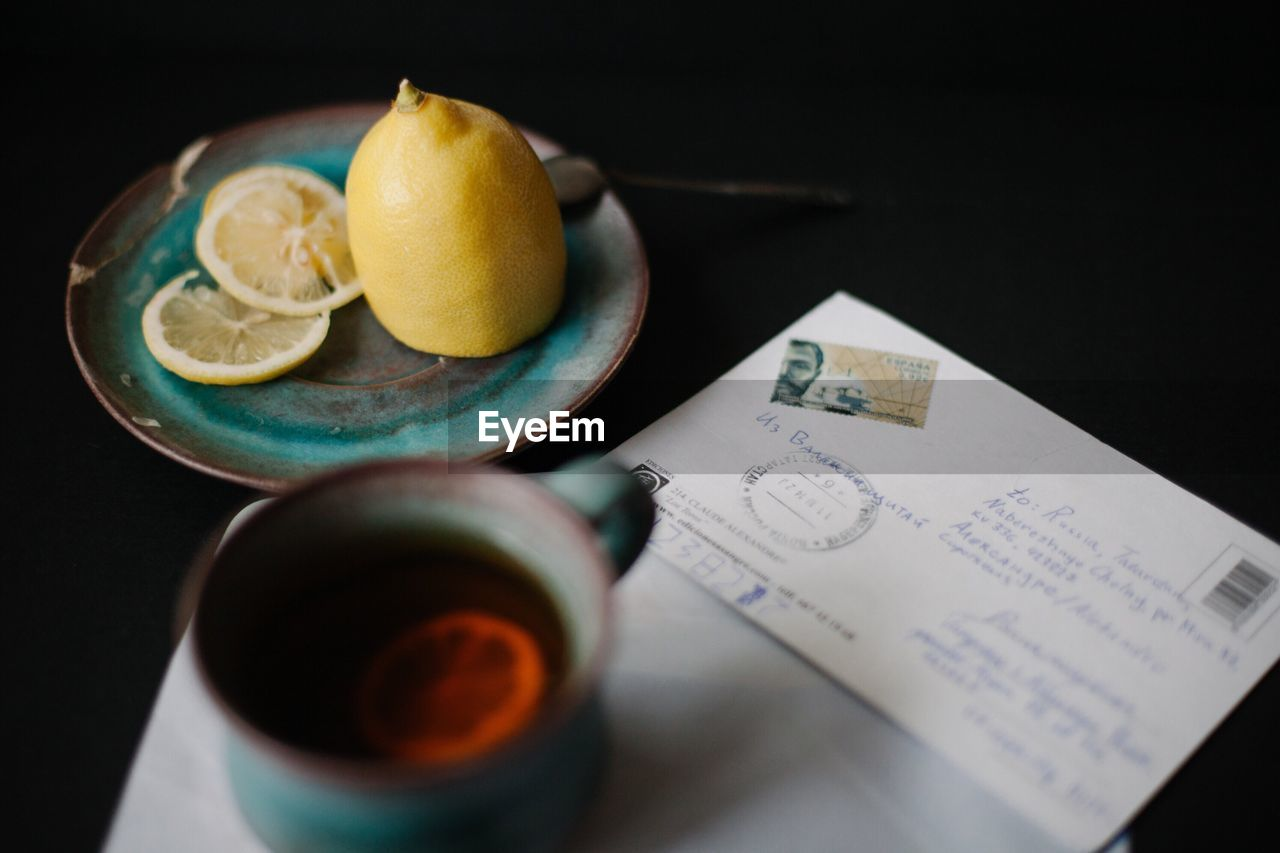 Close-up of lemon tea on table with envelope