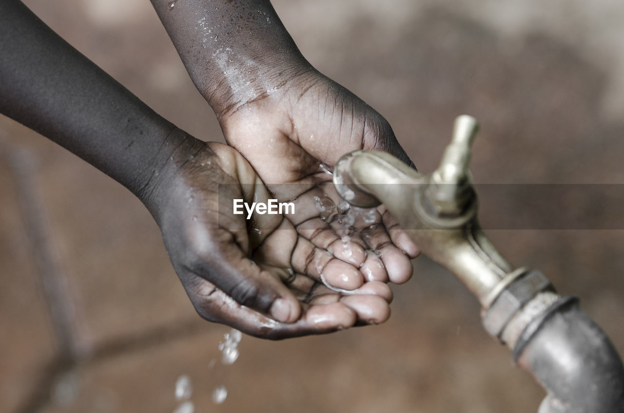 Close-up of hands under falling water from faucet
