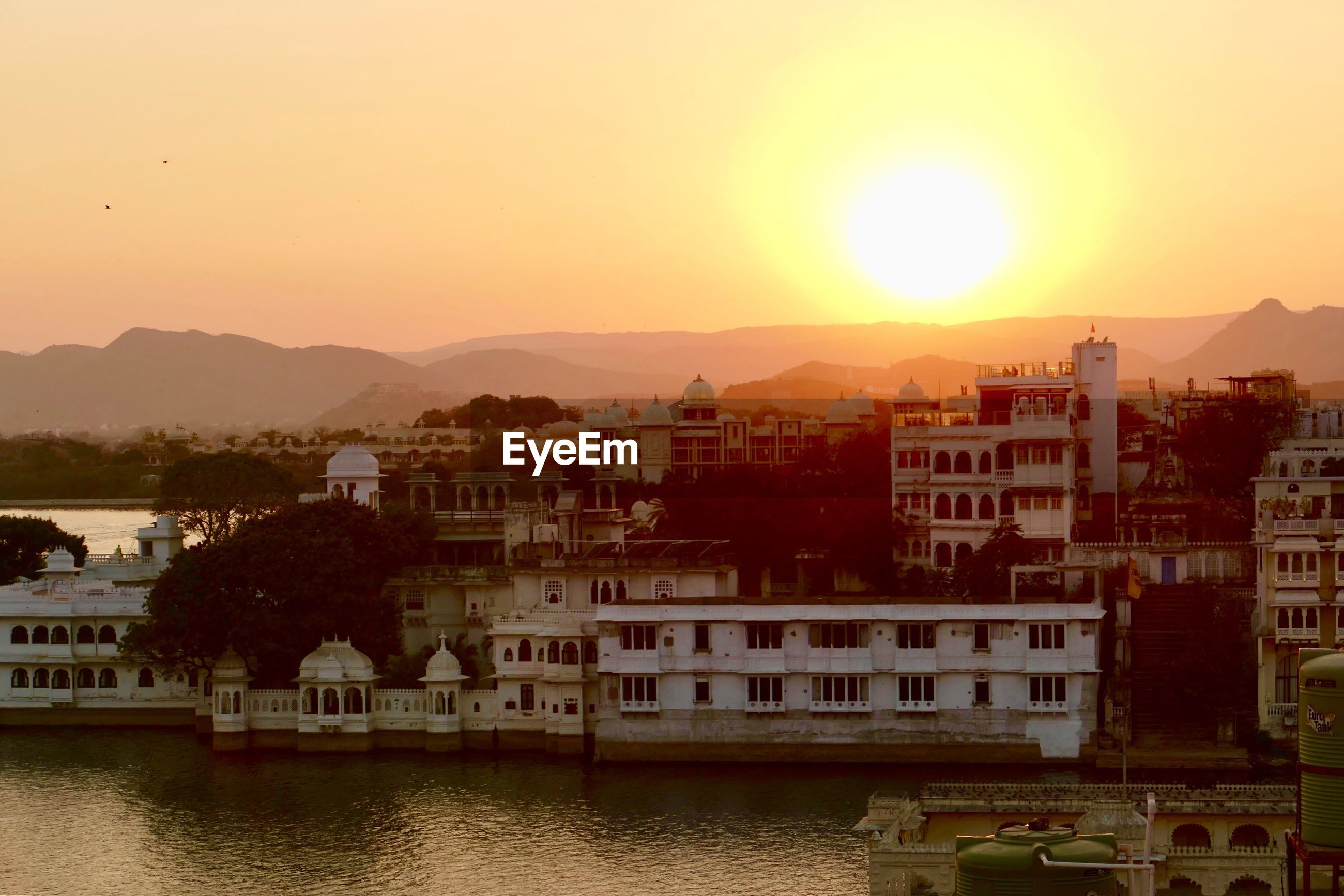 VIEW OF TOWNSCAPE BY RIVER AGAINST SKY DURING SUNSET