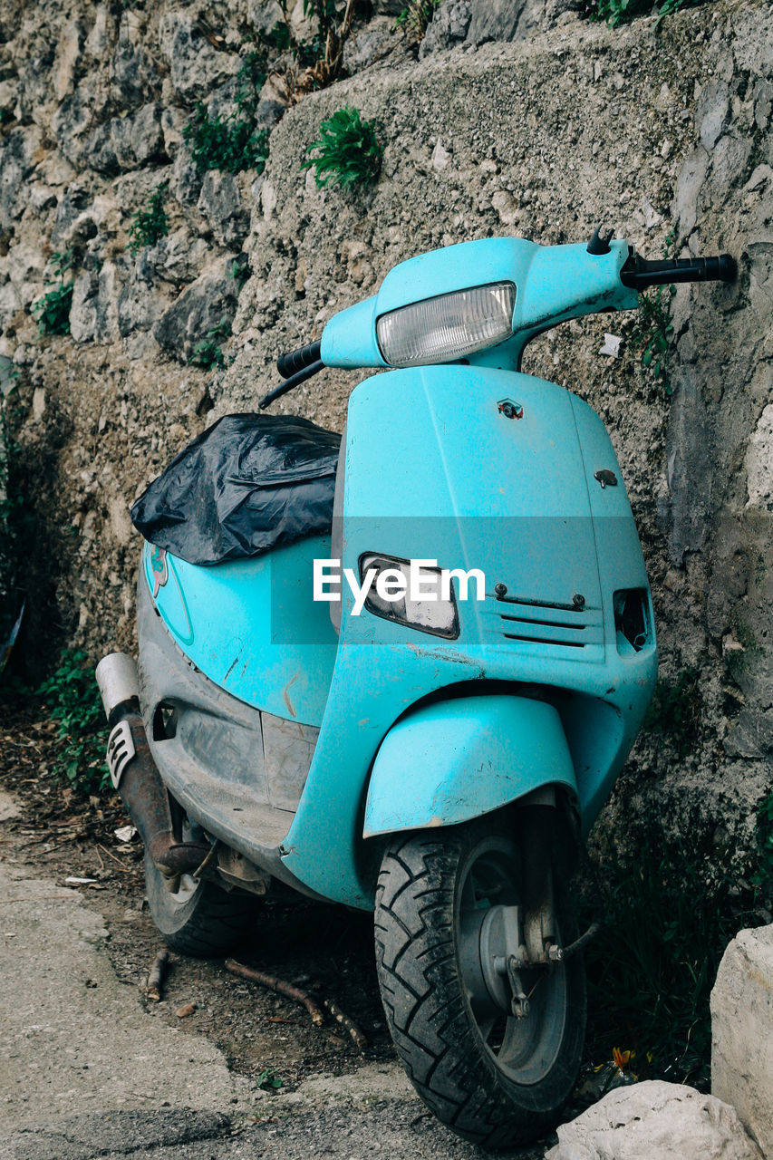 Abandoned motor scooter parked by stone wall