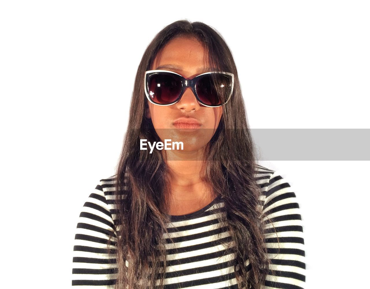 Portrait of woman wearing sunglasses against white background