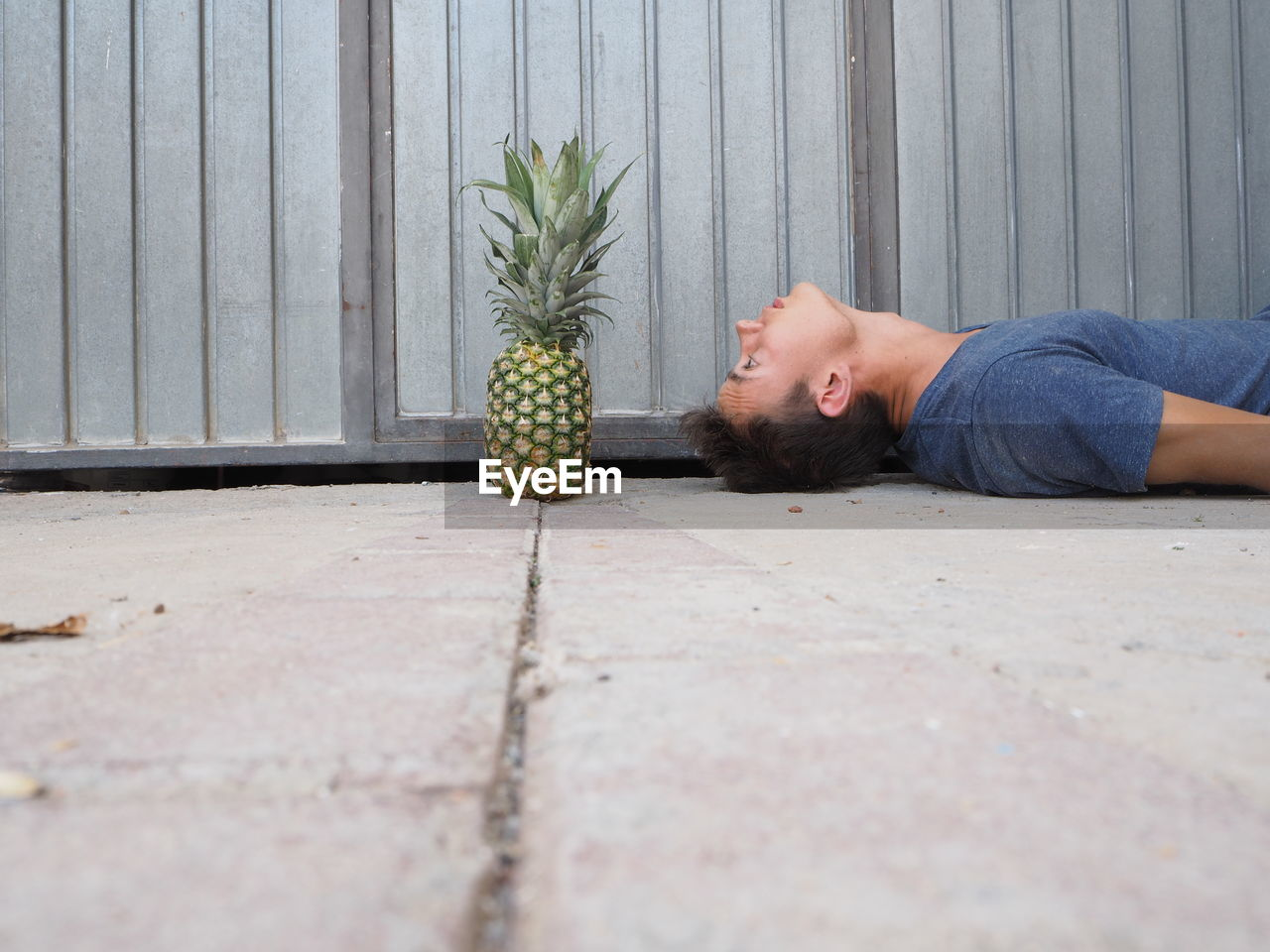 Surface Level Of Young Man Looking At Pineapple While Lying On Footpath