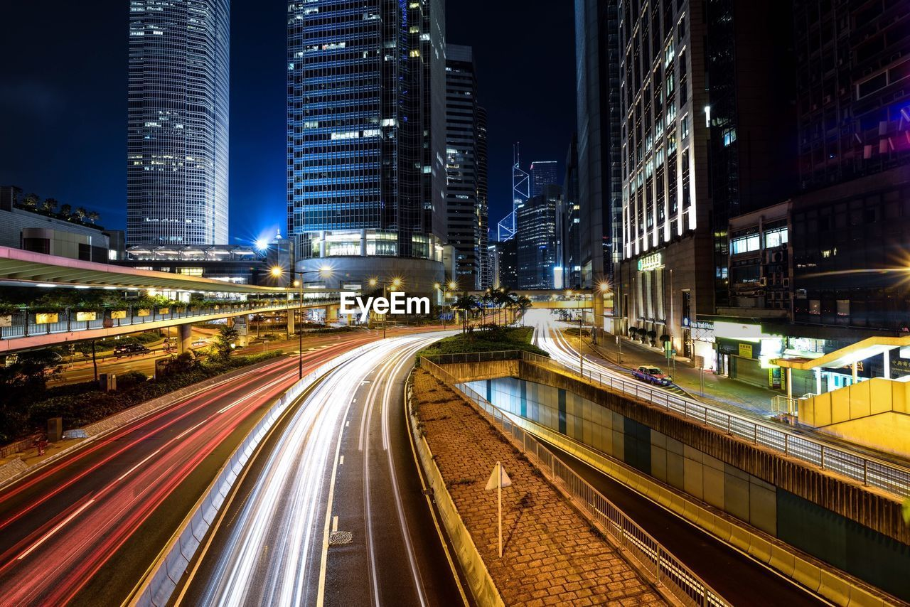 night, illuminated, building exterior, motion, long exposure, architecture, city, speed, light trail, transportation, skyscraper, blurred motion, built structure, modern, city life, travel destinations, outdoors, no people, road, cityscape, sky