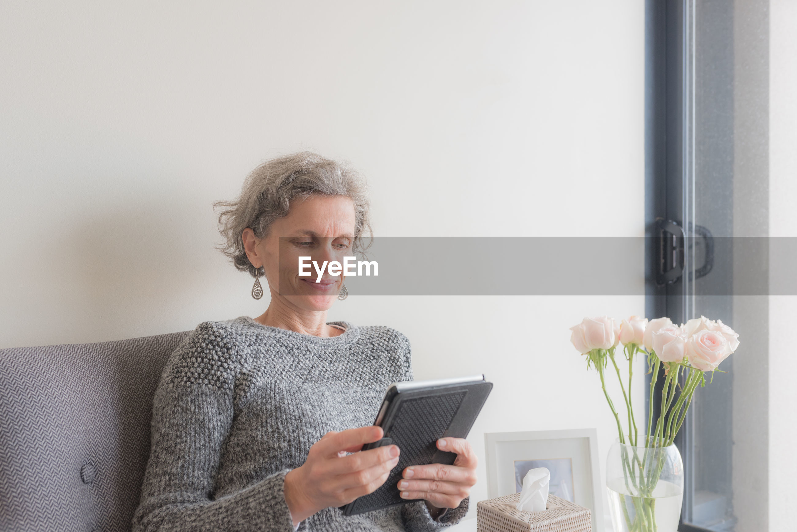 Smiling woman using digital tablet while sitting on chair at home