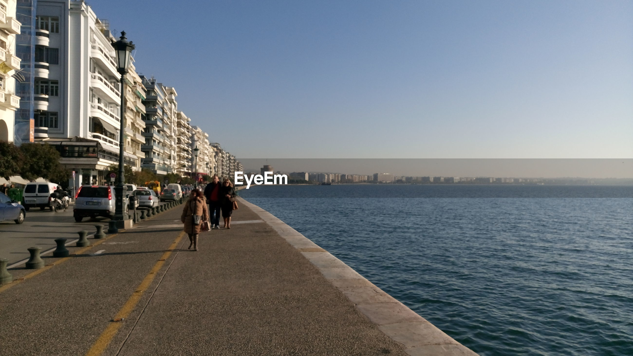 WOMEN WALKING ON WATER BY BUILDINGS AGAINST CLEAR SKY
