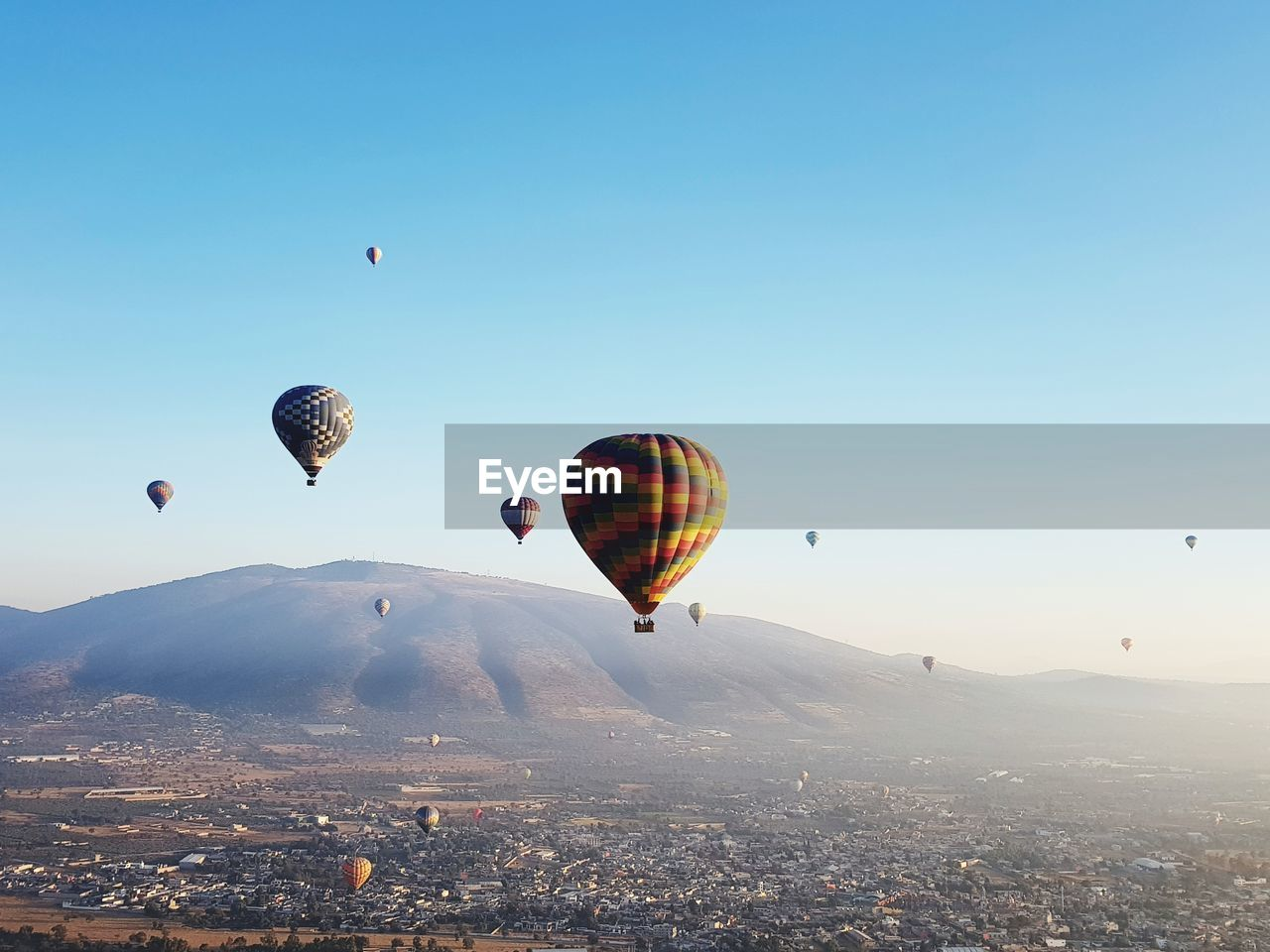 hot air balloon, air vehicle, flying, mid-air, balloon, sky, transportation, adventure, nature, architecture, city, clear sky, building exterior, travel, mode of transportation, parachute, ballooning festival, built structure, extreme sports, cityscape, no people, outdoors