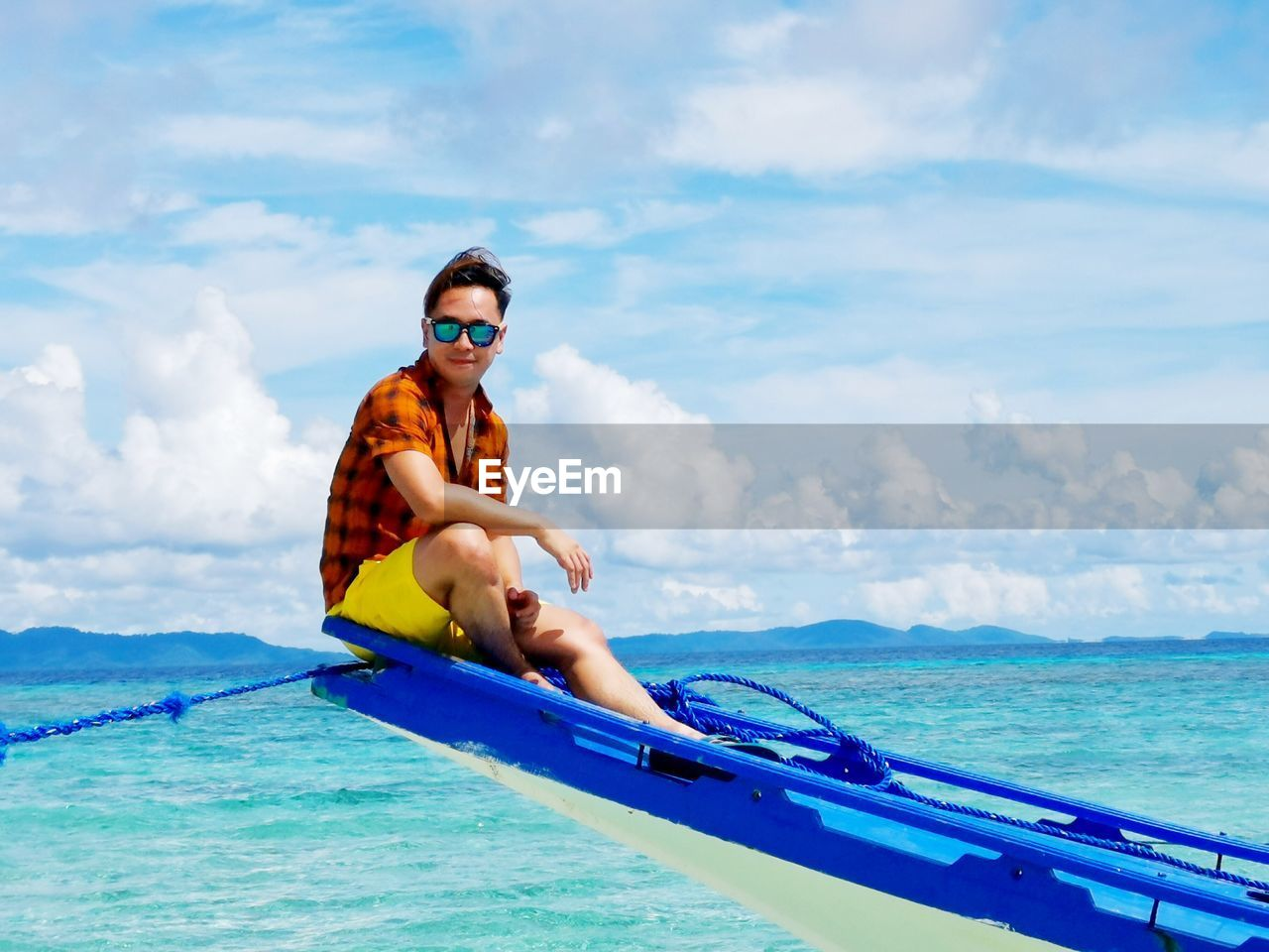Portrait of man sitting on boat in sea against sky