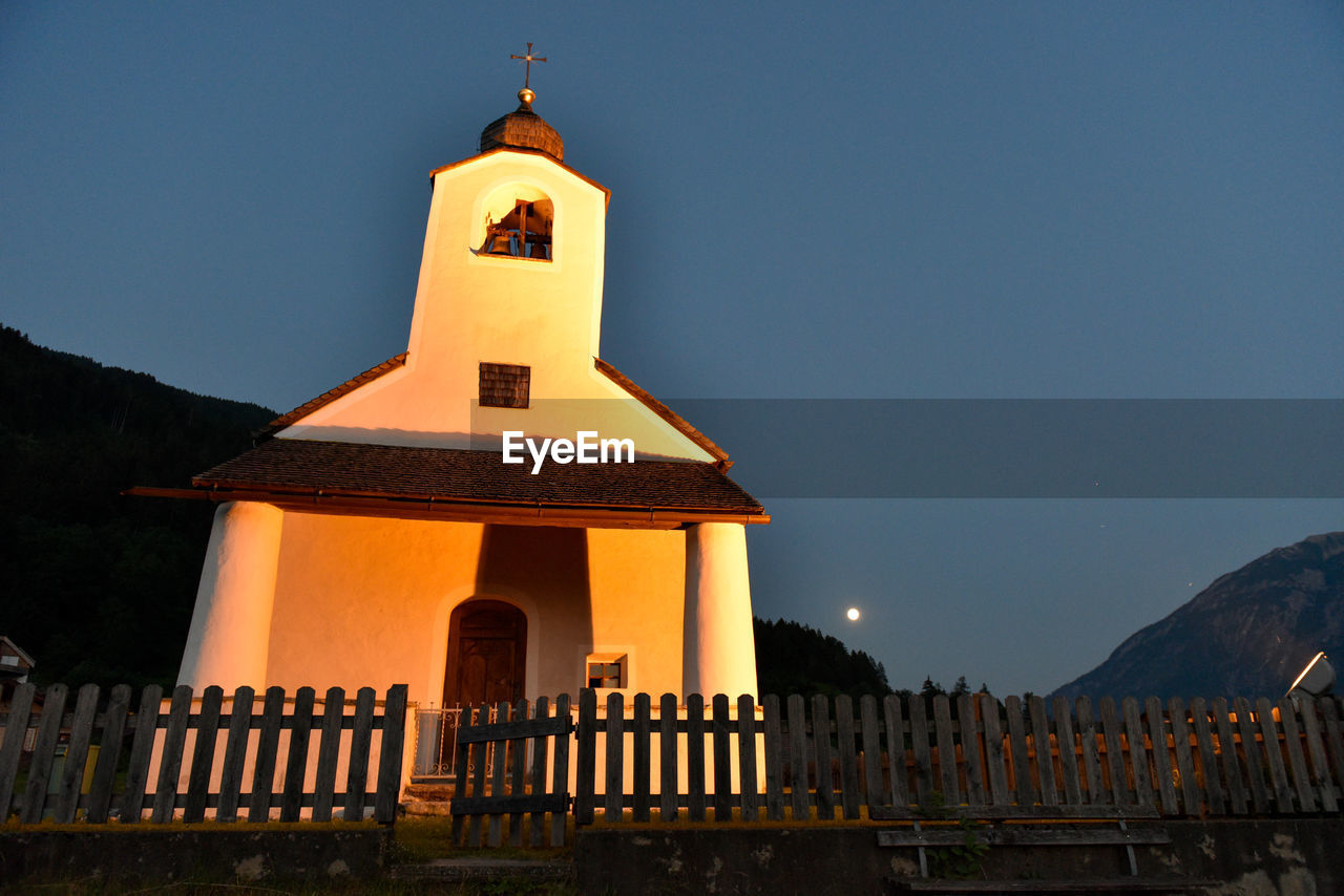 religion, spirituality, place of worship, architecture, built structure, tower, mountain, bell tower, cross, no people, outdoors, building exterior, sky, low angle view, sunset, day