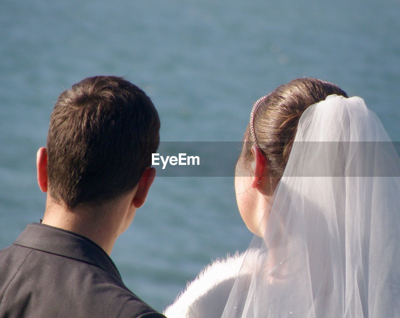 Rear view of newlywed couple looking at sea