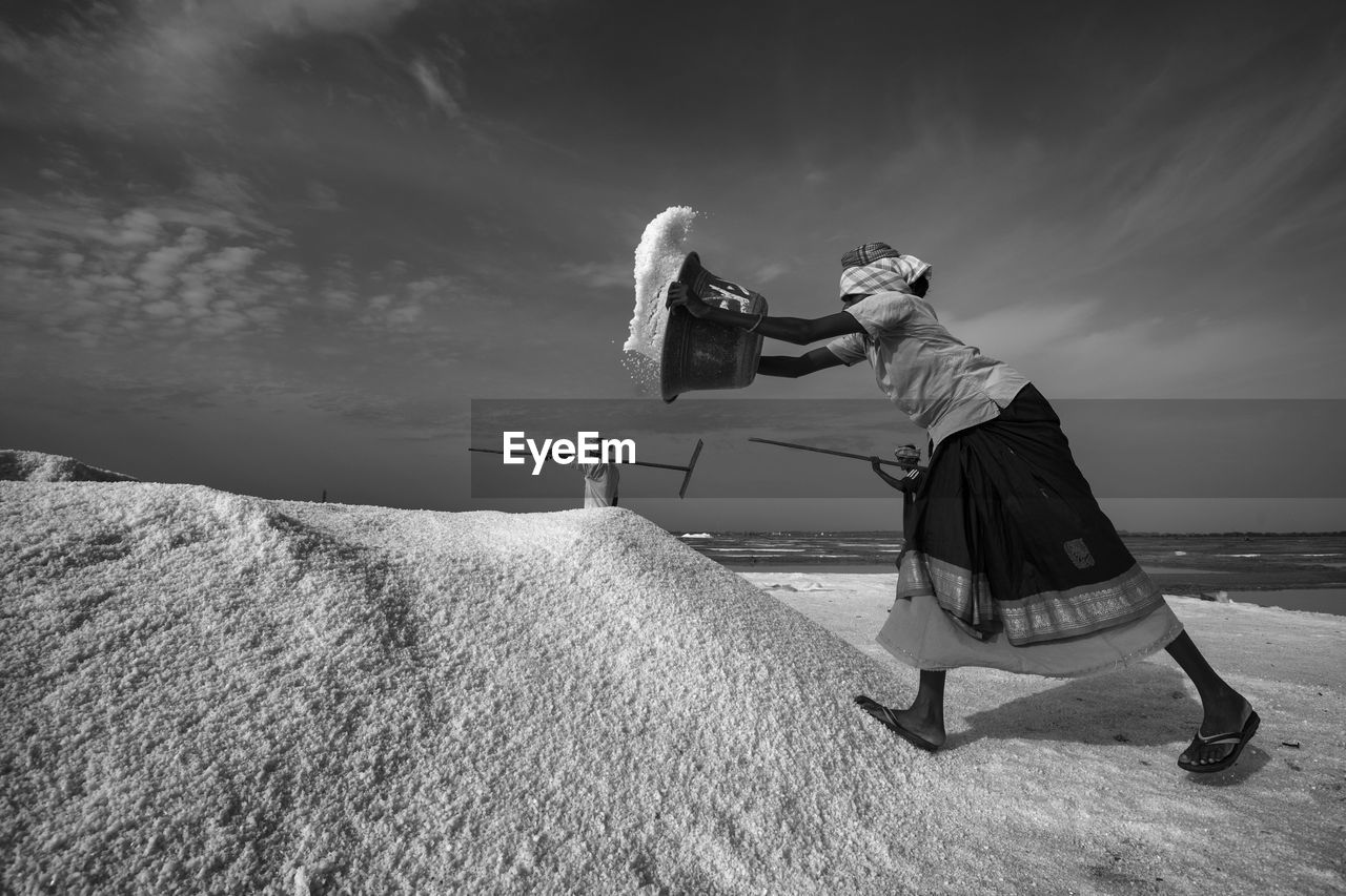 Woman Working At Salt Flat Against Sky