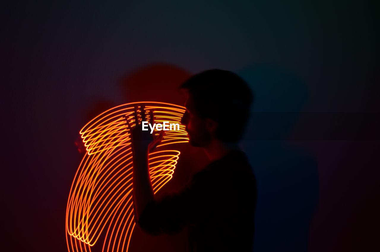 Silhouette man standing by illuminated lighting equipment at night
