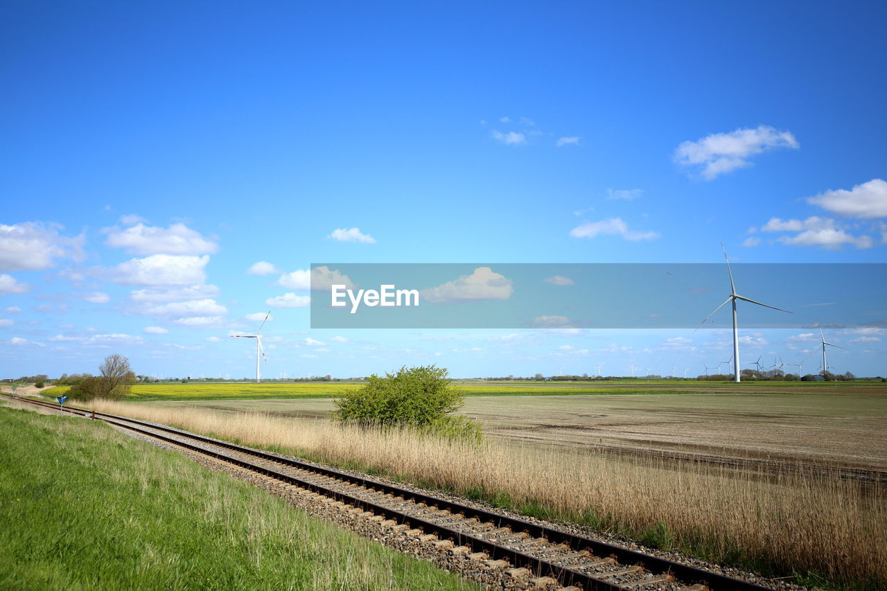 sky, environment, rail transportation, field, transportation, grass, blue, plant, land, nature, day, landscape, railroad track, cloud - sky, fuel and power generation, no people, track, environmental conservation, turbine, beauty in nature, outdoors