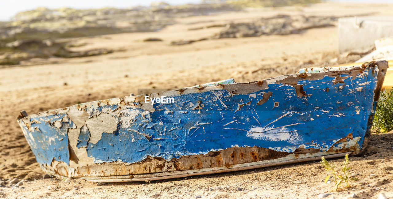 land, no people, day, blue, focus on foreground, wood - material, nature, outdoors, metal, close-up, damaged, field, selective focus, abandoned, sunlight, beach, old, sand, bad condition, dirt