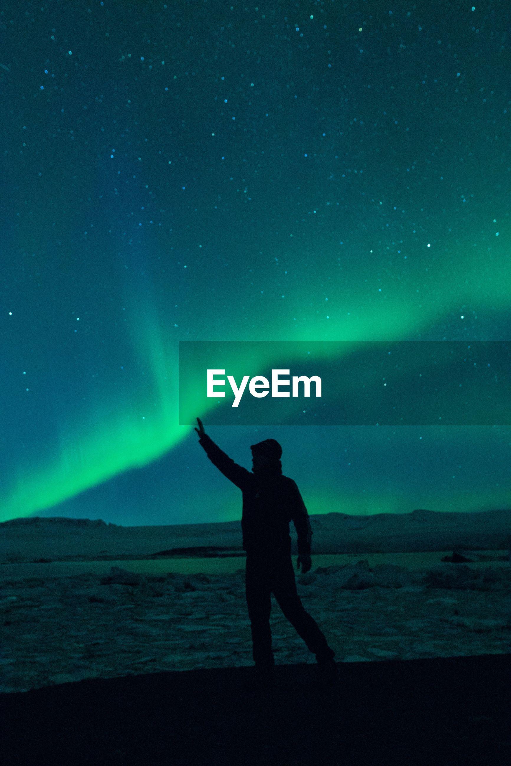 Optical illusion of silhouette man touching aurora borealis in sky