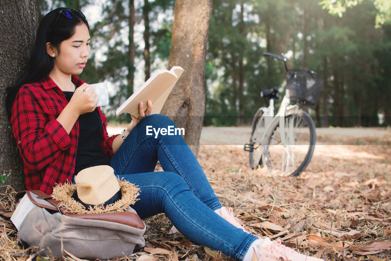 sitting, one person, holding, casual clothing, day, jeans, full length, relaxation, outdoors, leisure activity, real people, tree, young adult, book, park - man made space, young women, women, lifestyles, nature, beautiful woman, one young woman only, adult, people, adults only