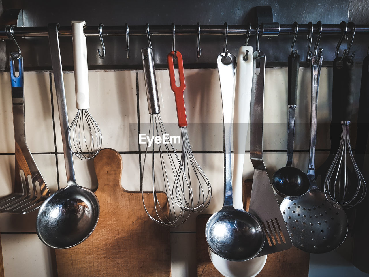 Close-up of utensils hanging on hooks in kitchen
