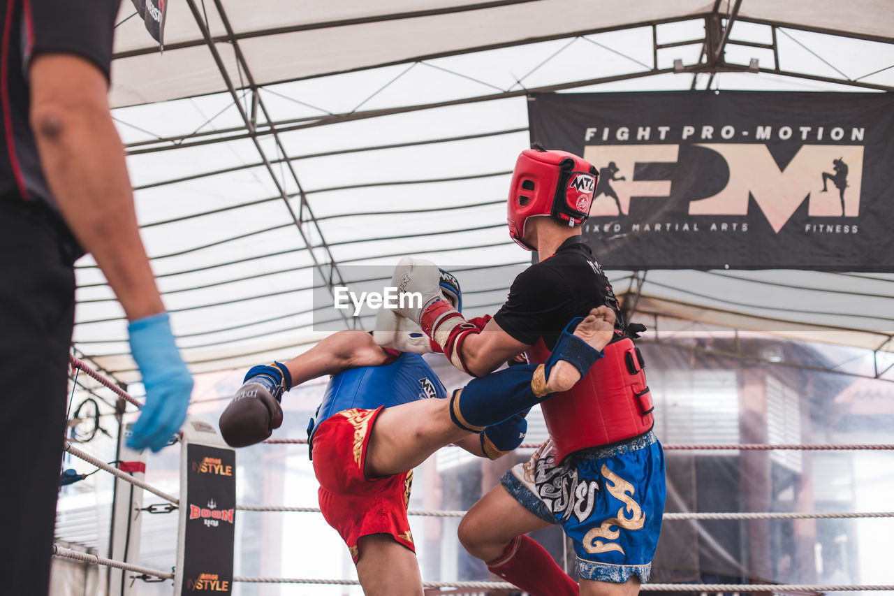 sport, lifestyles, strength, real people, men, vitality, group of people, clothing, day, people, indoors, boxing - sport, healthy lifestyle, exercising, boxing glove, athlete, standing, adult, sports clothing, three quarter length, effort