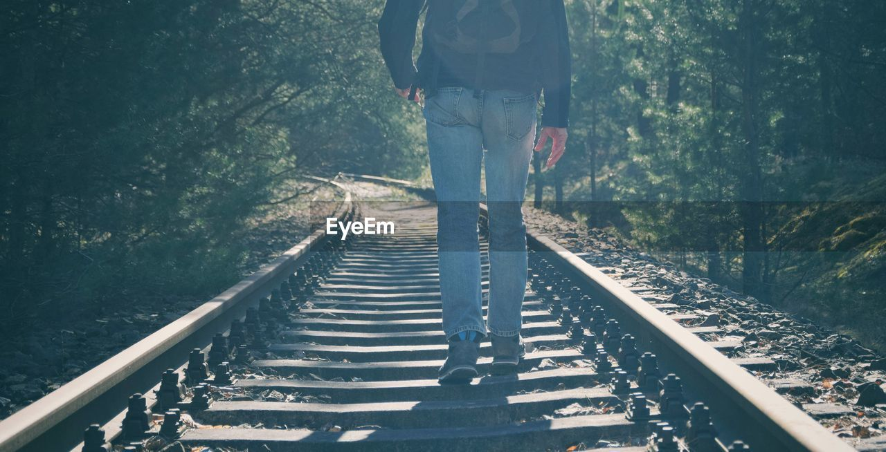 Low Section Of Man Walking On Railroad Tracks