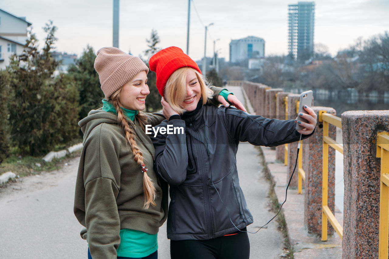 Women talking selfie while standing outdoors
