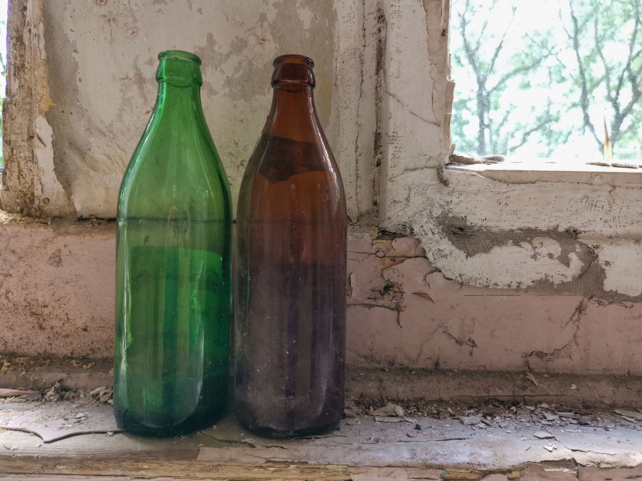 Close-up of empty bottles on windowsill against wall