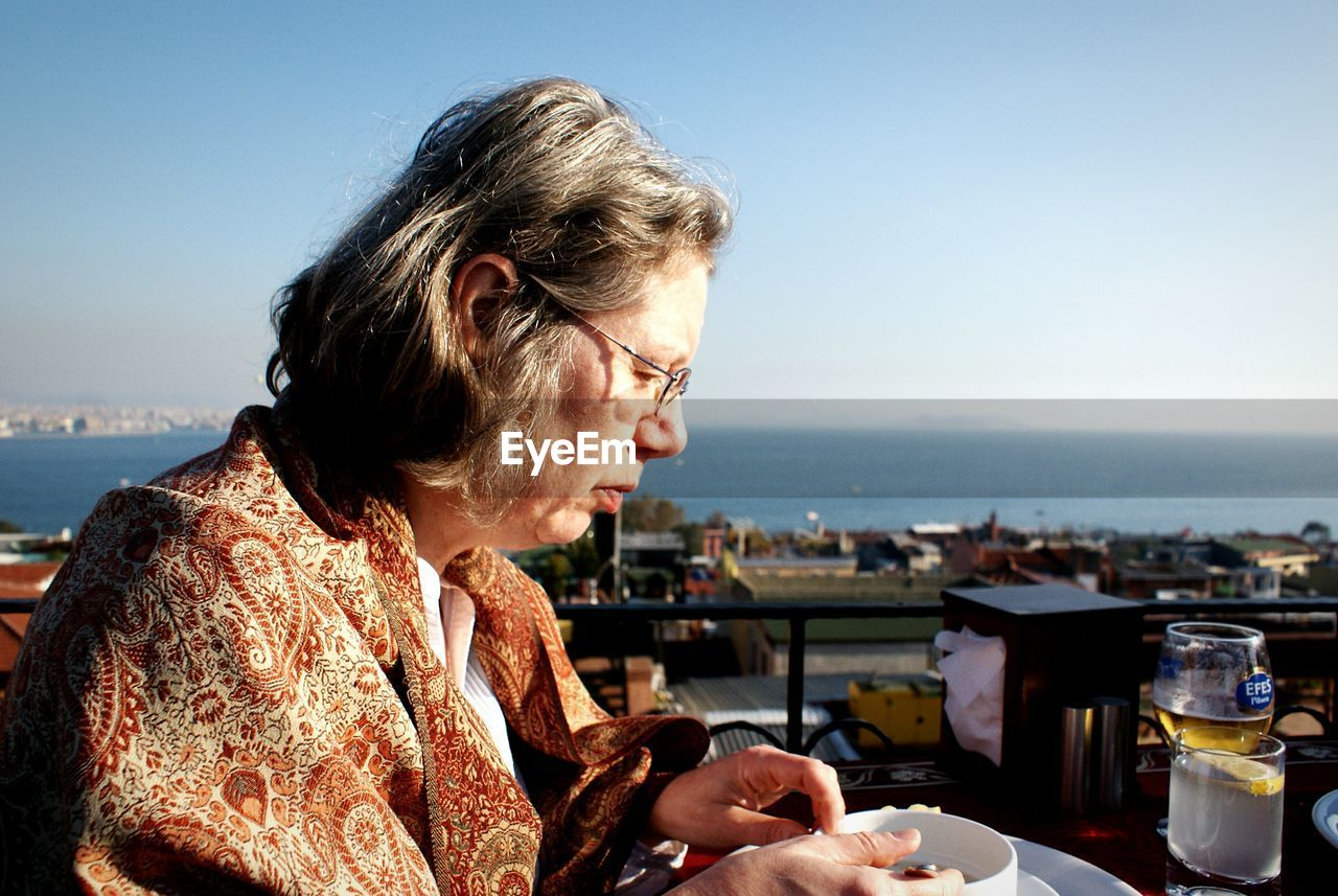 Side View Of Mature Woman Drinking Coffee At Cafe Against Sky