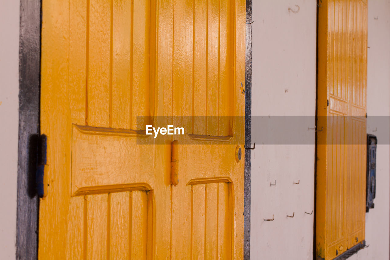 wood - material, yellow, built structure, architecture, no people, pattern, building, building exterior, protection, security, day, wall - building feature, door, safety, entrance, outdoors, close-up, closed, house