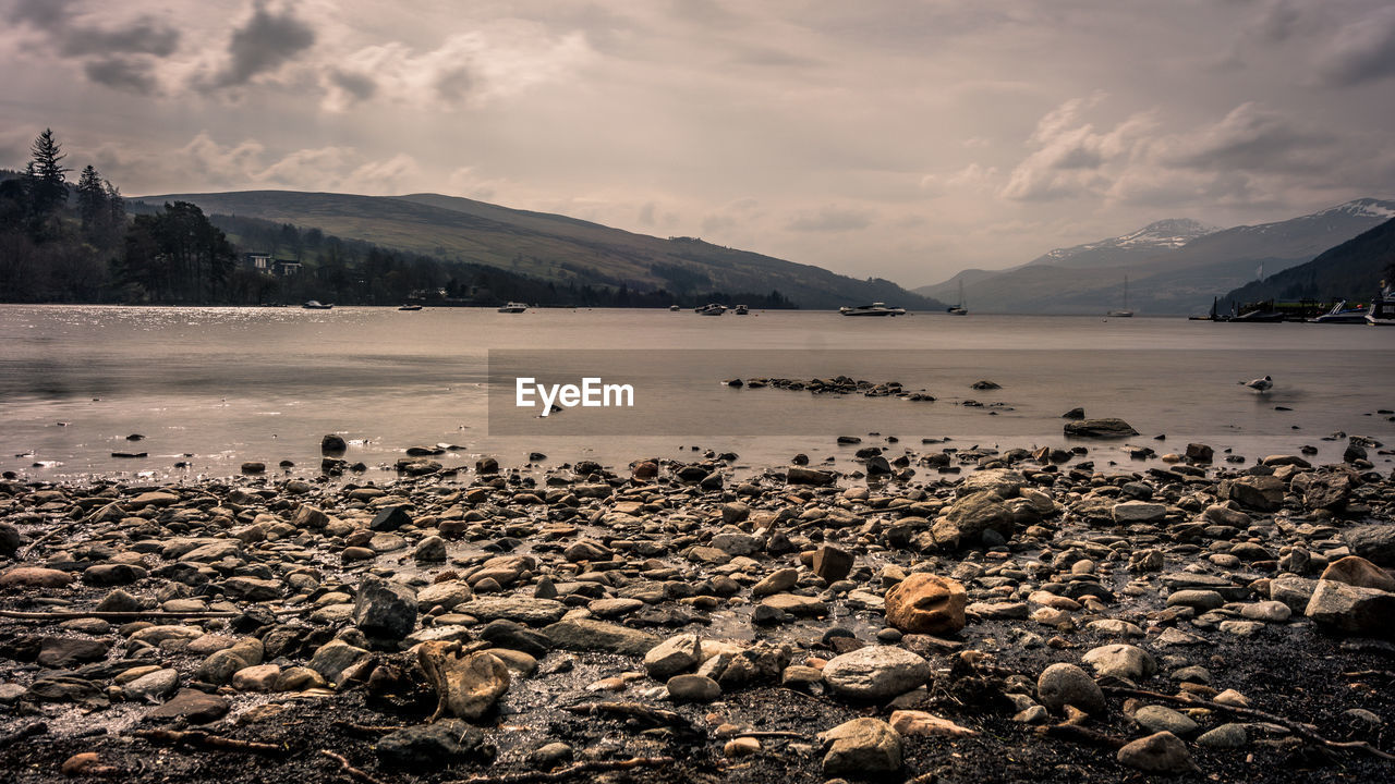 sky, cloud - sky, water, tranquil scene, beauty in nature, rock, scenics - nature, tranquility, mountain, beach, solid, land, nature, no people, sea, day, rock - object, non-urban scene, outdoors, pebble