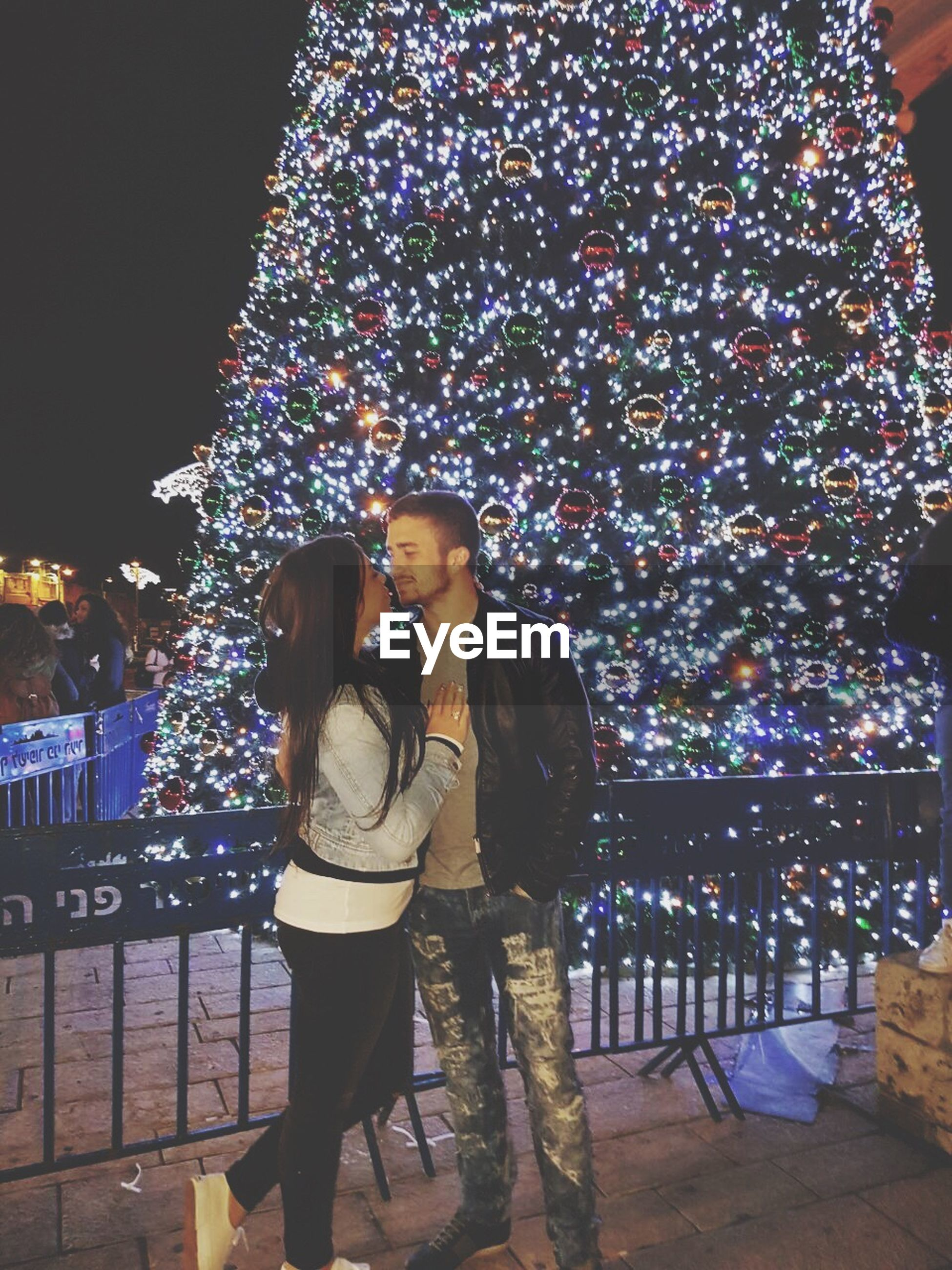 two people, night, christmas, lifestyles, illuminated, leisure activity, city, real people, young women, nightlife, party - social event, christmas decoration, christmas lights, celebration, adults only, beautiful woman, young adult, women, people, christmas tree, togetherness, outdoors, sky, adult
