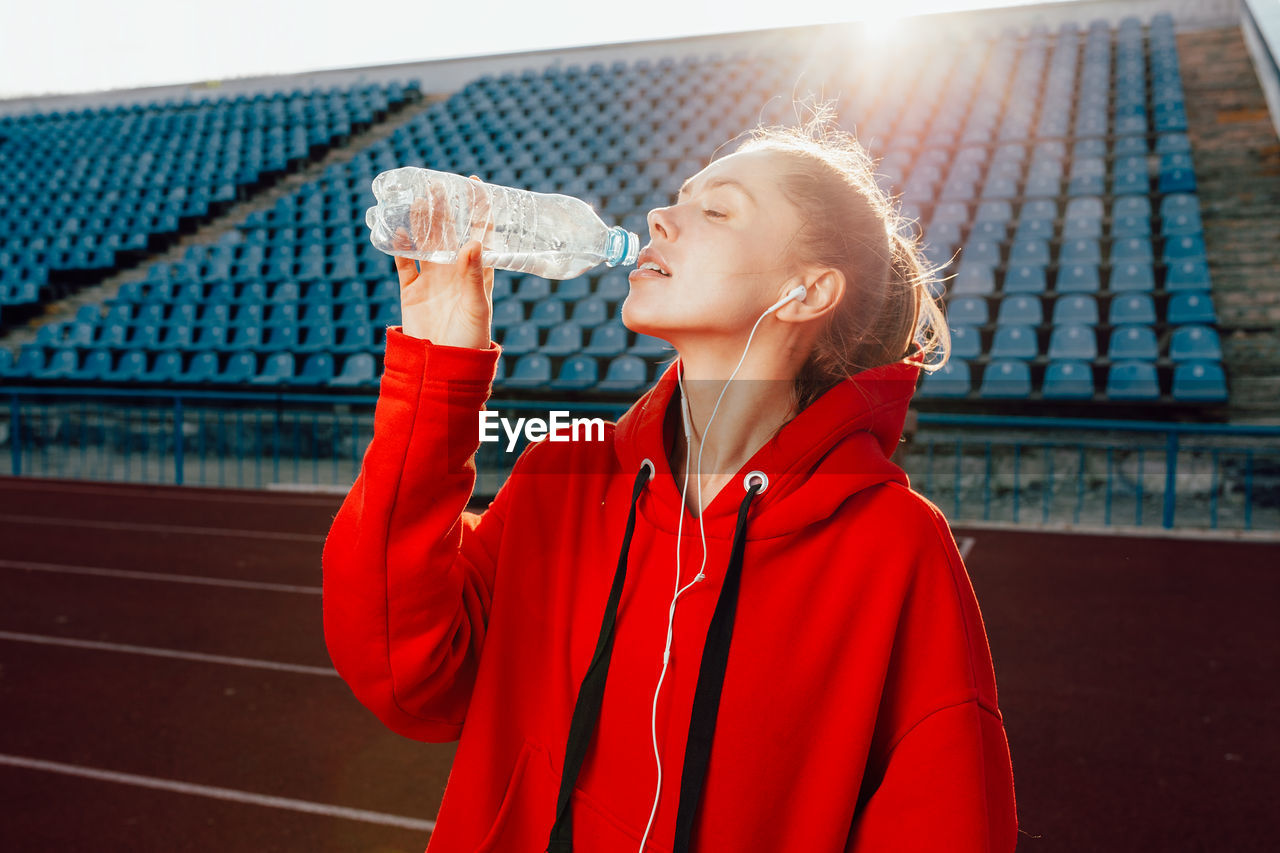 Female Athlete Drinking Water While Standing On Running Track