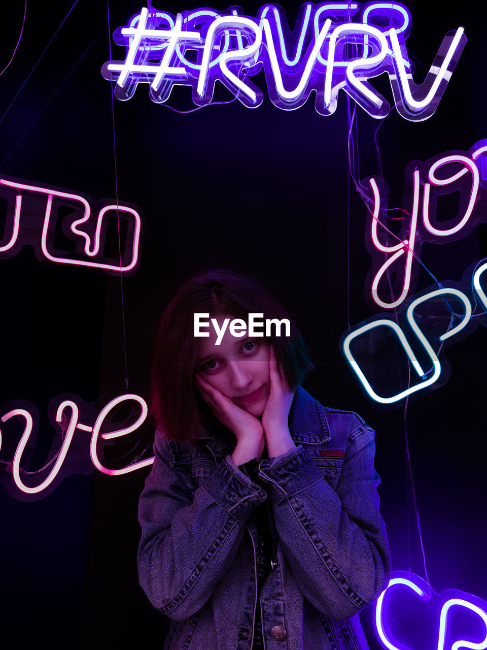 Portrait of woman standing against illuminated neon lights