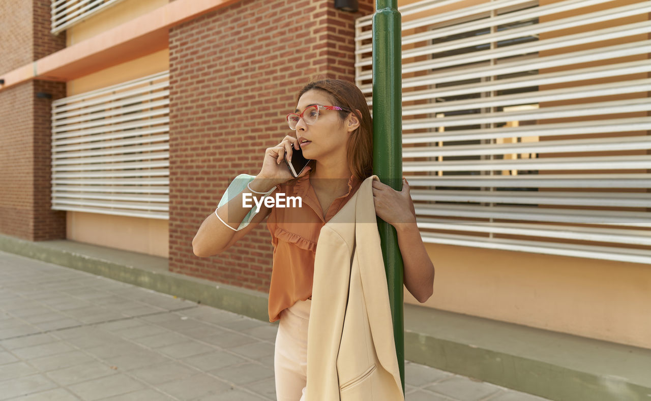 Young business woman talking on her cell phone outside commercial building