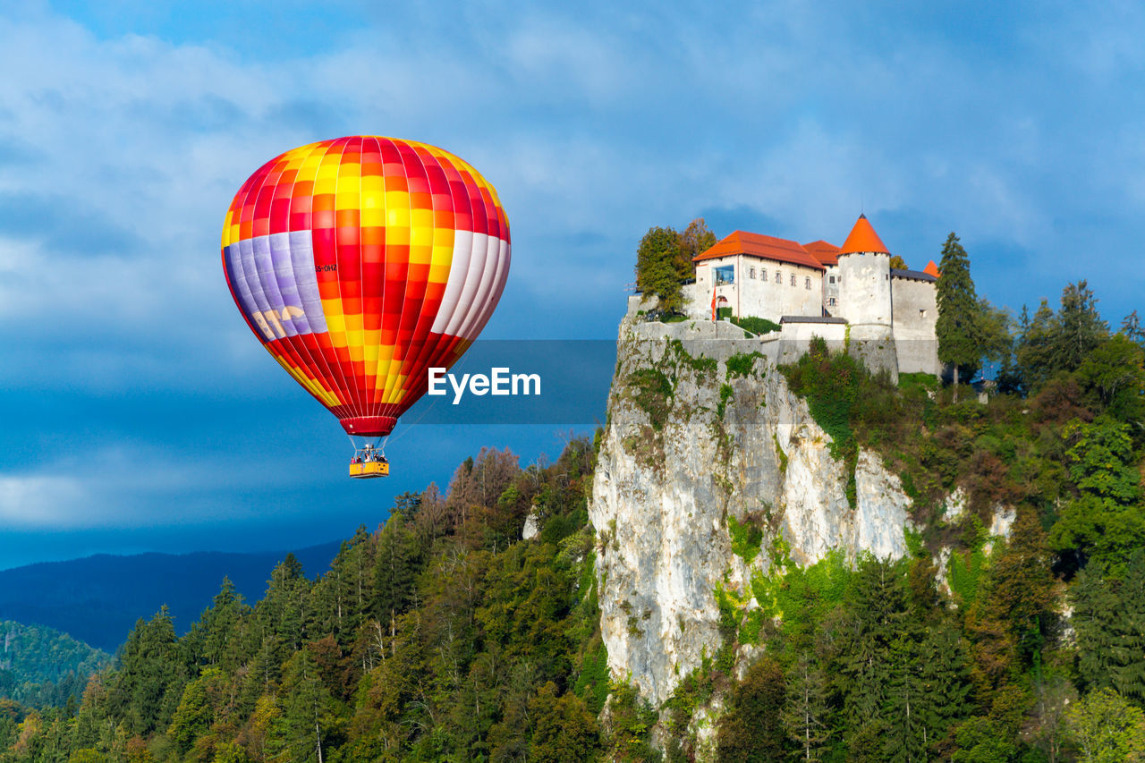 sky, mountain, nature, hot air balloon, balloon, tree, air vehicle, plant, cloud - sky, architecture, mid-air, beauty in nature, scenics - nature, transportation, flying, built structure, day, adventure, building exterior, low angle view, no people, outdoors, ballooning festival